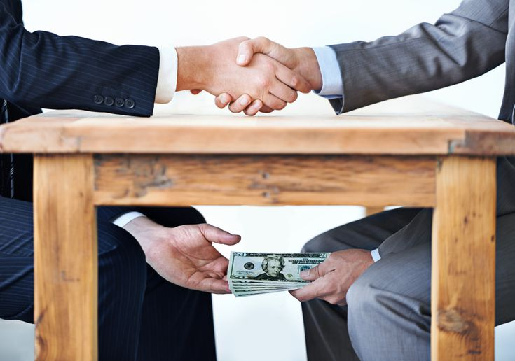 A two people sitting at table exchanging money under the table